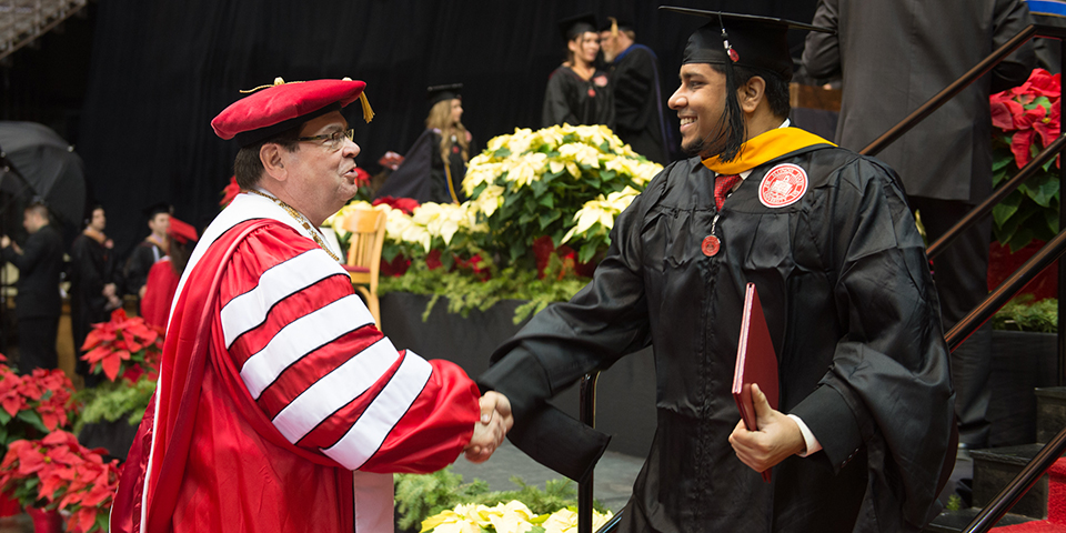 Dr. Dietz shaking hands with a graduate